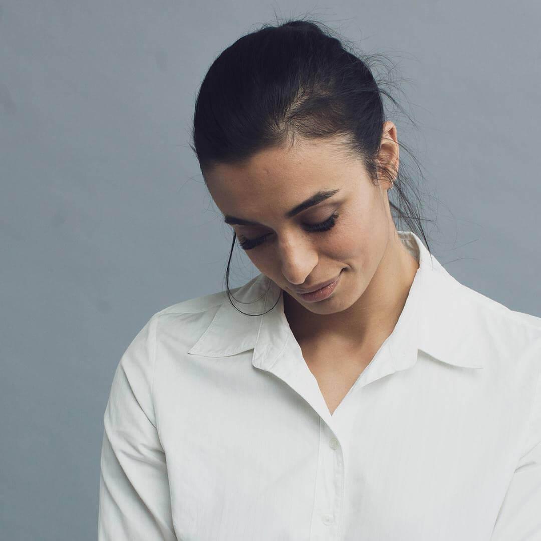 Eyewonderlust Taking Care of Eyelash Extensions Blog - Woman with Long Black Eyelashes Looking Down Head Down